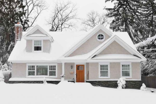 snow covered house with pinetrees